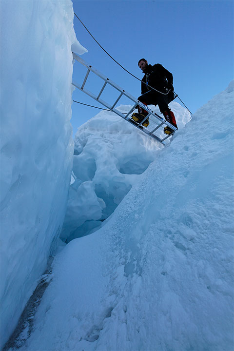 Andy climbs a ladder in the icefall